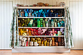 An old yarn or thread cabinet. A set of shelves with curtains, containing wools, yarn, haberdashery, and spools of lint, organised by color. Arranged in a colour pattern., Threads arranged in colour order.