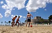 Three teenagers playing football on the beach at Castello in Manfredonia, Gargano, Apulia, Italy