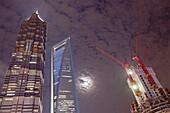 Baustelle des neuen Shanghai Tower neben Shanghai World Financial Center und Jin Mao Tower bei Nacht, Pudong, Shanghai, China, Asien