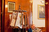 Man reading newspaper from newspaper stand, Cafe Tomaselli, Salzburg, Austria