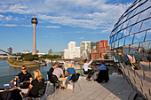 People at the terrace of a restaurant at media harbour, view to Rhine tower and Neuer Zollhof, Duesseldorf, North Rhine-Westphalia, Germany, Europe