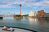 Couple sitting on a terrace at media harbour, view o Rhine tower and Neuer Zollhof with Gehry buildings, Duesseldorf, North Rhine-Westphalia, Germany, Europe