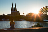 Young woman sitting on the Rhine river banks opposite to the cathedral, Cologne, North Rhine-Westphalia, Germany, Europe