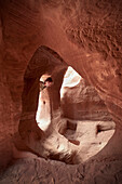 Archaeology student looking into cave tomb in Petra, UNESCO world heritage, Wadi Musa, Jordan, Middle East, Asia