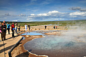 Tourists at one geyser hole in the valley of Haukadalur at the golden circle, Iceland, Europe