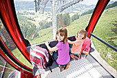 Two girls sitting in cable car, Allgaeu, Bavaria, Germany