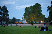 People sitting on the lawn underneath giant plantain tree at Alter Zoll beer garden in the evening, Bonn, North Rhine-Westphalia, Germany, Europe
