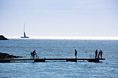 Silhouette of sailing boat on the horizon, bicycle and people on a pier, Visby, Gotland, Sweden, Europe
