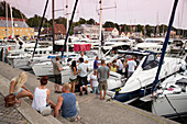People celebrating aboard a yacht at marina, Visby, Gotland, Sweden, Europe