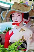 A geisha in a summer kimono wearing a strange hat