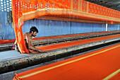 India, Rajasthan, Saree factory, Worker laying 150 m long sarees before printing