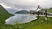 young woman jumping over the fjord Bergsfjorden Landscaping of the National Tourist Route The west coast of the island Senja has been selected as one of the most spectacular landscapes in Norway Senja island County of Troms, Norway, Northern Europe