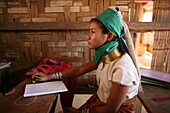 A young Longneck girl sits at a desk at school Approximately 300 Burmese refugees in Thailand are members of the indigenous group known as the Longnecks The largest of the three villages where the Longnecks live is called Nai Soi, located near Mae Hong So