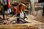 A Longneck woman prepares reeds for weaving or thatch Approximately 300 Burmese refugees in Thailand are members of the indigenous group known as the Longnecks The largest of the three villages where the Longnecks live is called Nai Soi, located near Mae
