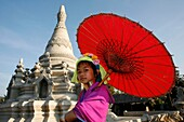 A young Longneck girl holding a parasol in front of a temple in Mai Soi Approximately 300 Burmese refugees in Thailand are members of the indigenous group known as the Longnecks The largest of the three villages where the Longnecks live is called Nai Soi
