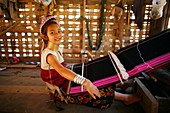 A young Longneck girl smiles as she weaves cloth on a loom Approximately 300 Burmese refugees in Thailand are members of the indigenous group known as the Longnecks The largest of the three villages where the Longnecks live is called Nai Soi, located near