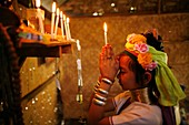 A young Longneck girls prays, holding a candle, at her family´s altar Approximately 300 Burmese refugees in Thailand are members of the indigenous group known as the Longnecks The largest of the three villages where the Longnecks live is called Nai Soi,.