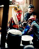 Oracle of Sabu, 77 year old healer Sonam Sangmu is treating a child in her kitchen near Leh, Ladakh, Jammu and Kashmir, India