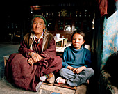 72 year old grandma of family Tsemopa with granddaughter, Ney near convent Thagchockling, Ladakh, Jammu and Kashmir, India