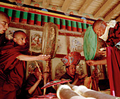 Monks with drums and wind instruments recieving blessed food during the Hemis Gonpa Festival at convent Hemis, southeast of Leh, Ladakh, Jammu and Kashmir, India