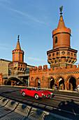 Red cabrio at the Oberbaum Bridge, Oberbaumbruecke over river Spree, architect Otto Stah, Kreuzberg, Berlin
