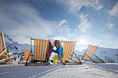 Couple sitting in deck chairs in snow, Kuehtai, Tyrol, Austria