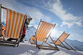Woman relaxing in a deckchair in snow, Kuehtai, Tyrol, Austria