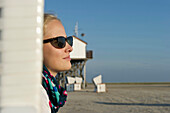 Young woman sitting in a beach chair, Sankt Peter-Ording, Wadden Sea National Park, Eiderstedt peninsula, North Frisian Islands, Schleswig-Holstein, Germany, Europe