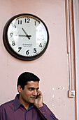 Indian talking on a mobile phone underneath a wall clock, Pune, Maharashtra, India
