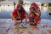 Girls praying, making a offering,in Gangaur ghat,Pichola lake,Udaipur, Rajasthan, india