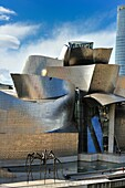 """'Vertical Image Guggenheim Museum in Bilbao with the sculpture of Louise Bourgeois, """"Mother"""" in the foreground and a museum maintenance worker climbing up the facade'"""