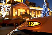 taxi outside belfast city hall illuminated with christmas lights and xmas market northern ireland uk