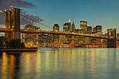 Brooklyn Bridge, East River, South Street Seaport, and lower Manhattan skyline at dusk, as seen from Brooklyn Bridge Park, New York City, New York, USA