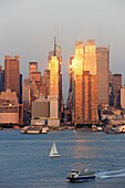 The setting sun reflects off the windows of Manhattan skyscrapers on 42nd street in New York City, New York, USA as viewed over the Hudson River from New Jersey