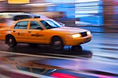 Motion blurred abstraction of taxi rushing through Times Square in New York City, New York, USA