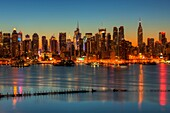 The Manhattan skyline in New York City during morning twilight as viewed over the Hudson River looking east from New Jersey. The cool blue eastern sky was accented with tinges of orange that began to show in the hour before sunrise.