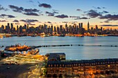 The Manhattan skyline in New York City during morning twilight as viewed over the Hudson River looking east from Weehawken, New Jersey. The eastern sky and clouds were accented with tinges of orange that began to show in the hour before sunrise.
