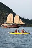 Kayakers paddle near a cruising junk Halong Bay Vietnam