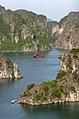 Cruising junk among rocky islands of Halong Bay Vietnam