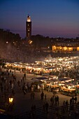 The La Koutoubia Mosque at Jemaa El Fna Square in Marrakech with food stalls and fruit sellers at nightime  Morroco