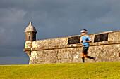 Jogger running past El Morro Fort in old San Juan Puerto Rico