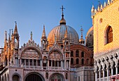 Warm glow of the setting sun on the detailed architecture of the Basilica San Marco in Venice, Veneto Italy