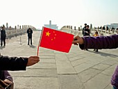 A visitor to the Forbidden City in Beijing, China, holds a Chinese flag