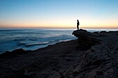 person stands on top of the rocks of the coastline at sunset time, Cadiz, Spain
