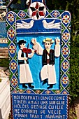 Tombstone showing a fiddler and a man doing a traditional dance, The Merry Cemetery  Cimitirul Vesel, Sapânta, Maramares, Northern Transylvania, Romania. The naive folk art style of the tombstones created by woodcarver Stan Ioan Patras 1909 - 1977