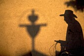 The shadow of a man wearing a hat and cycling is cast with a cross in a wall in San Gregorio Atlapulco cemetery, Xochimilco, Mexico City. The Day of the Dead celebration is a tradition that honors the deceased