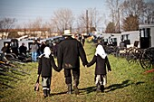 Amish man walks with his children past dozens of buggies ready for auction during the Annual Mud Sale to support the Fire Department in Gordonville, PA