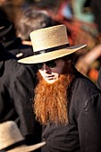 Amish man with a red beard bids on farm equipment during the Annual Mud Sale to support the Fire Department in Gordonville, PA