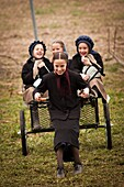 Amish girls play on a carriage during the Annual Mud Sale to support the Fire Department in Gordonville, PA