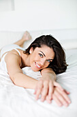 Portrait of a pretty woman in bed smiling at camera